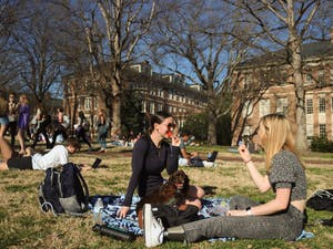 First-year students Kelly Ray and Sarah Prosser enjoy some strawberries on Polk Place on Feb. 25, 2021.