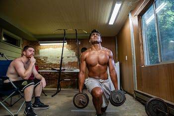 UNC club rugby players Neeral Patel (right) and Philip Patterson (left) work out in the basement of their home in Chapel Hill on Sept. 1, 2020. They have had to figure out ways to train on their own since gyms closed statewide in March due to COVID-19 restrictions.