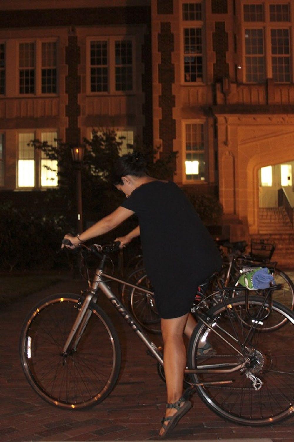 <p>Senior Global Studies major Eileen Harvey rides her bike in front of Memorial hall on Thursday night.</p>