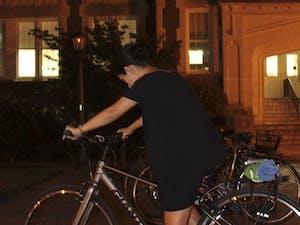 Senior Global Studies major Eileen Harvey rides her bike in front of Memorial hall on Thursday night.
