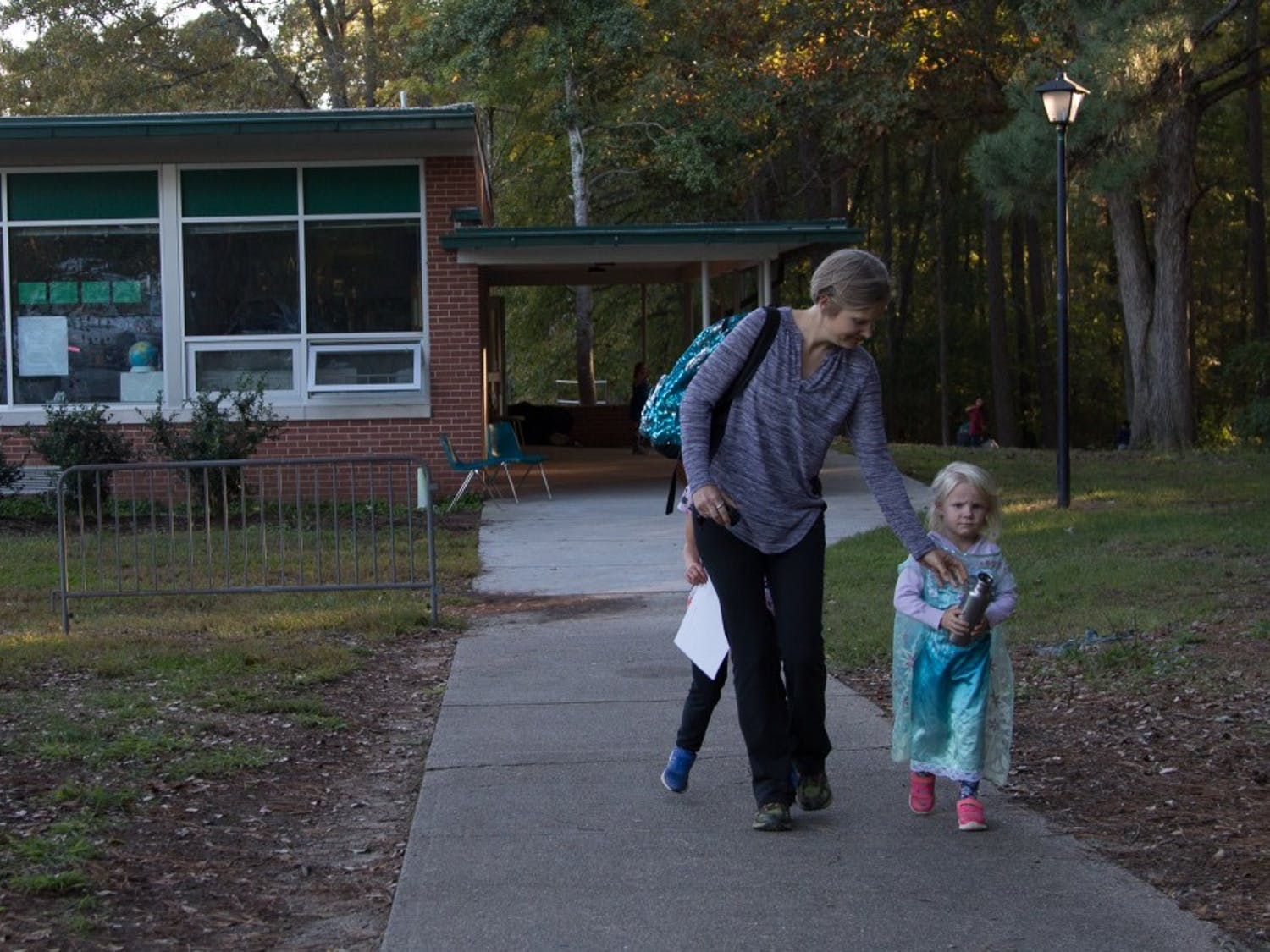 """Becca Wright, parent of 2 Glenwood children, Eaden and Elsa leaves with her daughter Mable after school on Tuesday Oct. 30. """"I'm just glad the program isn't ending"""". Wright says as her children run circles around her."""