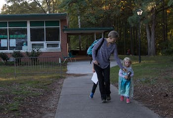 "Becca Wright, parent of 2 Glenwood children, Eaden and Elsa leaves with her daughter Mable after school on Tuesday Oct. 30. ""I'm just glad the program isn't ending"".  Wright says as her children run circles around her."