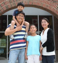 Jae Joong Kim, Stephano Kim (6 years old), Ji Yoon Kim (11 years old), Jung Mi Choi sit in front of Mary Scroggs Elementary School. The kids spend a lot of their time at school and love every minute of it. One of Kim's main goals in studying in America for a year was for his family to improve his English.