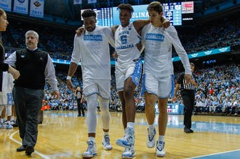 Junior forward Brandon Huffman (42) and junior forward Walker Miller (42) help first-year forward Armando Bacot (5) off the court after an injury in the game against Ohio State on Wednesday, Dec. 4, 2019. UNC lost to Ohio State 74-49.