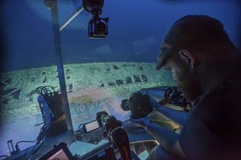 Joe Hoyt, Maritime Archaeologist with the NOAA Office of National Marine Sanctuaries, takes photos of the shipwreck from the submersible. Image courtesy of Carmichael, Project Baseline - Battle of the Atlantic expedition.