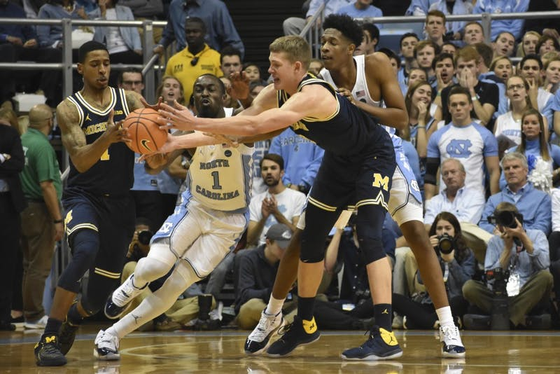 Theo Pinson (1) and Sterling Manley (21) reach to defend a Michigan handoff at the Dean Smith Center on Nov. 30.