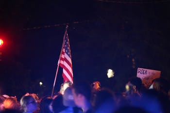 A protestor holds an American flag in the middle of the crowd.