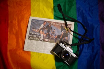 DTH Photo Illustration. A copy of the Daily Tar Heel and a film camera sit on top of a rainbow pride flag.