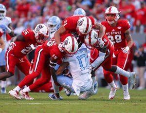 Wide receiver Anthony Ratliff-Williams (17) is swarmed by N.C. State defenders on Nov. 25 in Raleigh.