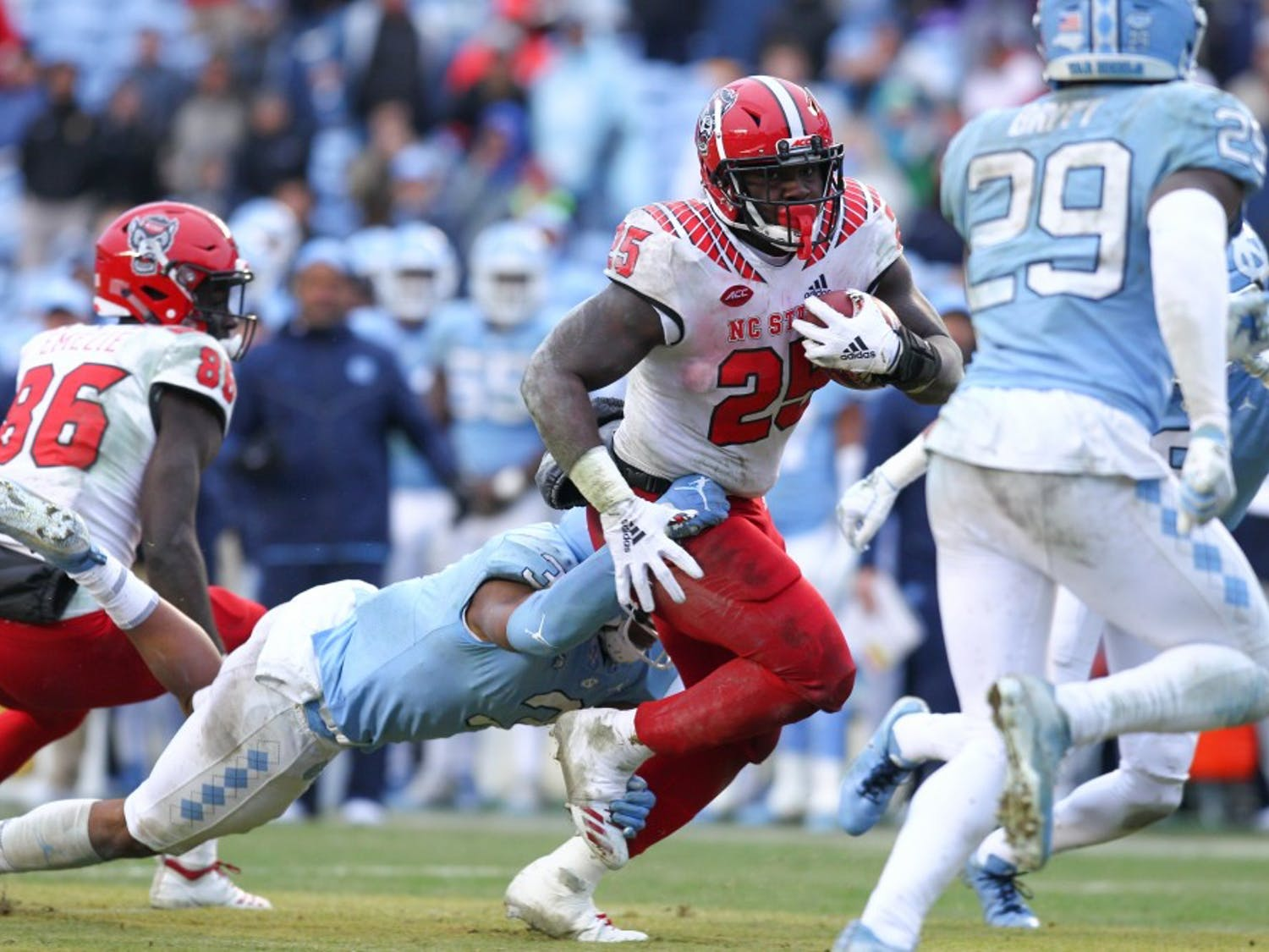 NC State running back Reggie Gallaspy II (25) tries to escape UNC players on Saturday, Nov. 24, 2018 in Kenan Memorial Stadium. NC State beat UNC 34-28 in overtime.