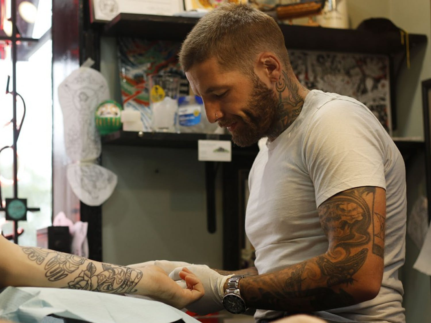 Mike Wheeler prepares Hayden Fitzgerald's arm before shading in his tattoo.