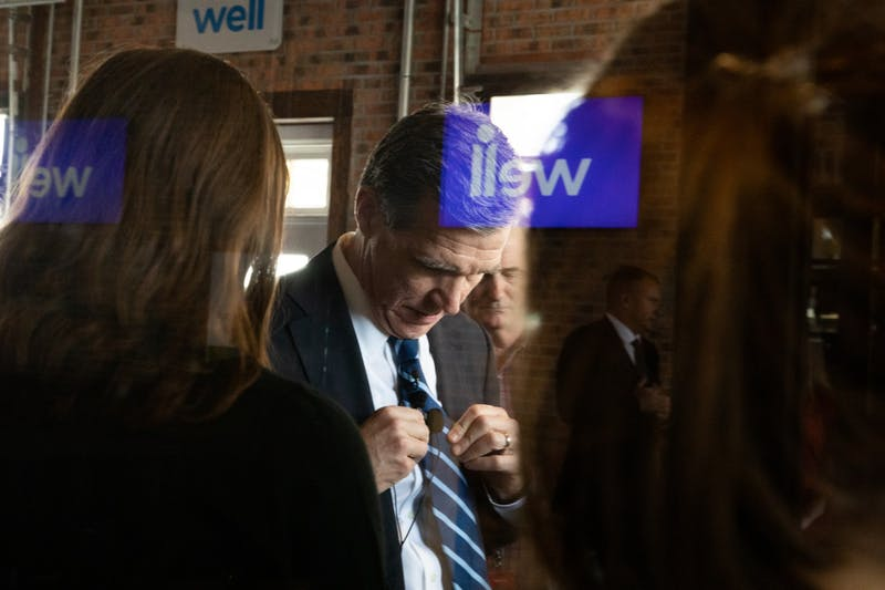Gov. Roy Cooper unclips a microphone from his tie as the logo of health technology company  Well Dot Inc. is reflected in glass following a press conference introducing the company to Chapel Hill on Tuesday, Nov. 19, 2019.