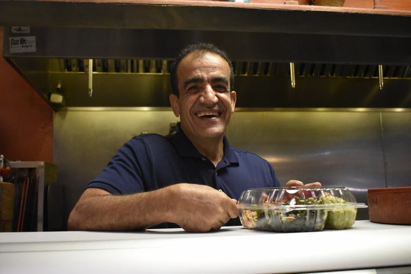 Jamil Kadoura, owner of Mediterranean Deli, smiles as he finishes preparing a plate for a customer.