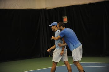 UNC tennis sophomore Benjamin Sigouin congratulates junior Ladd Harrison after competing in and winning in his first collegiate tennis match against Bucknell University on Saturday, Jan. 19. 2019.