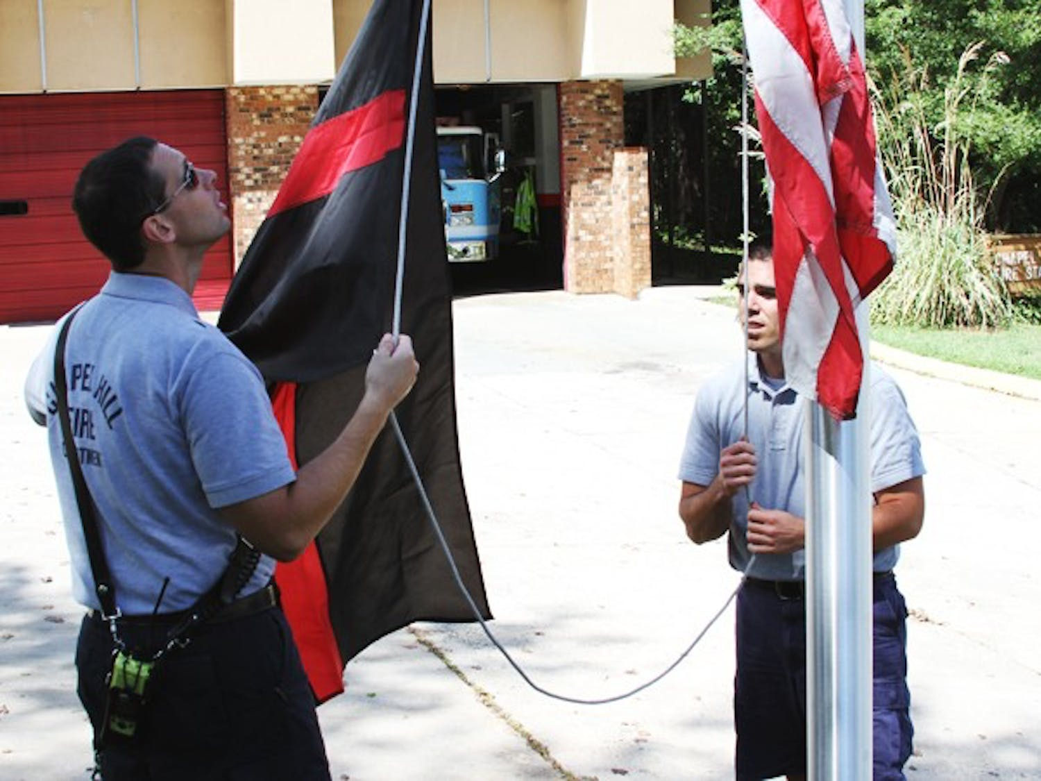 Chapel Hill fire department workers John Wellons (left) of Durham and Michael Crabtree (right) of Whitsett raise the fallen firefighters flag.
