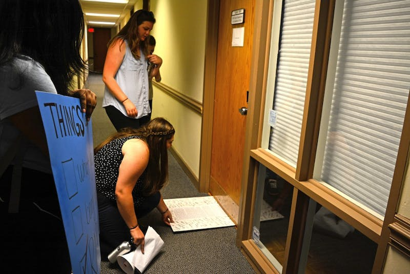 Sammie Espada, a junior women's and gender studies and poll sic double major, slides the letter under the door of the Equal Opportunity and Compliance Office, upon finding the office completely empty.
