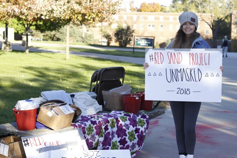 Cosette Hood, a member of Eastern Michigan University's student organization Unmasked, stands by the information table for the project.