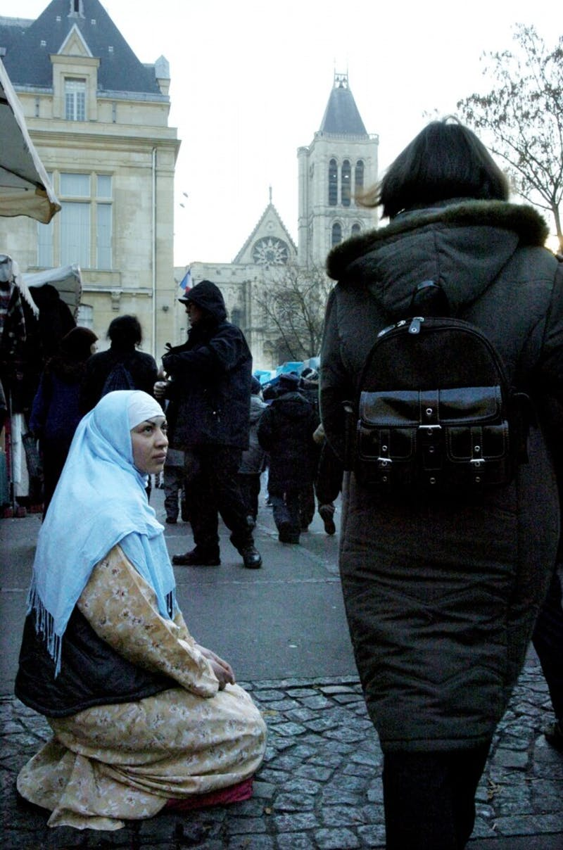 A young Muslim woman begs for money at an outdoor market in Saint-Denis, France.  In 2004, the French government imposed a law banning the public display of religion, including the hijab, in schools.