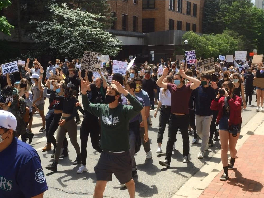 "Protester put their hands in the air chanting ""Hands up! Don't Shoot!"" as they march down the streets of Ann Arbor."
