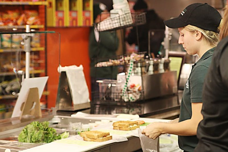 CrossRoads Deli employee Kari Caye prepares one of the shop's made-to-order sandwiches. The MarketPlace provides a higher end (and higher priced) student dining option.