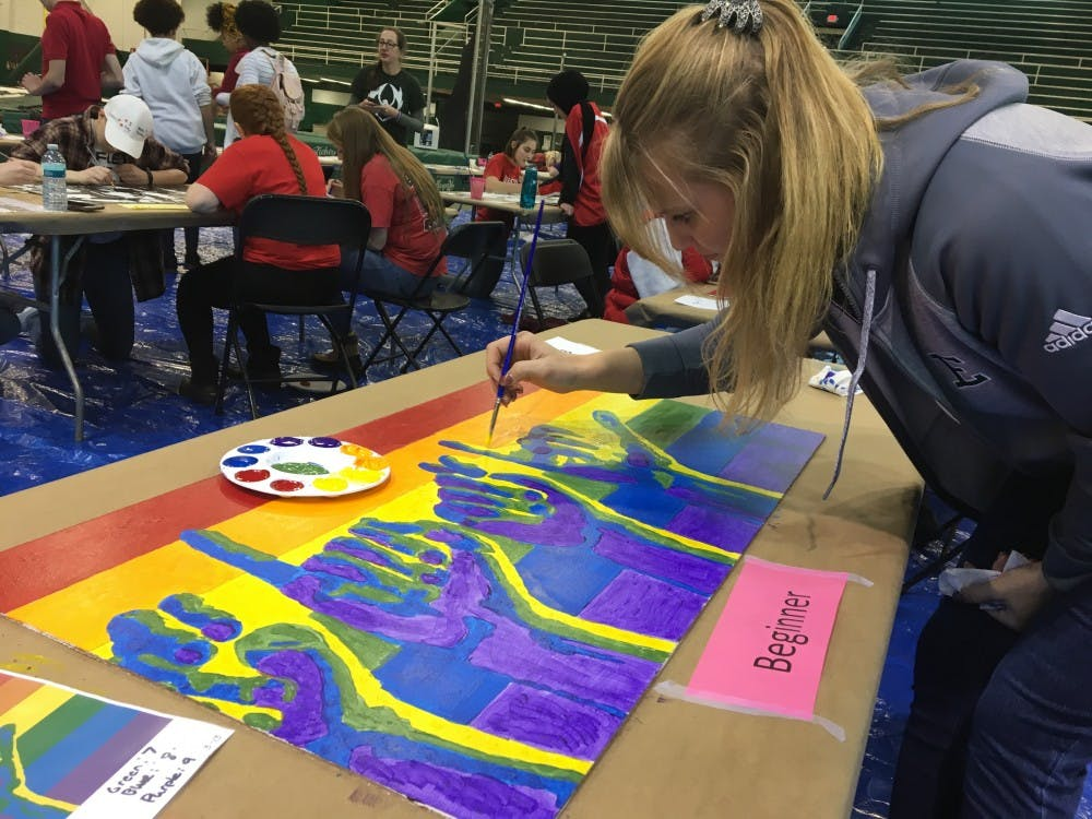 Student carefully colors in artist's work for the EMU's first Unity Mural