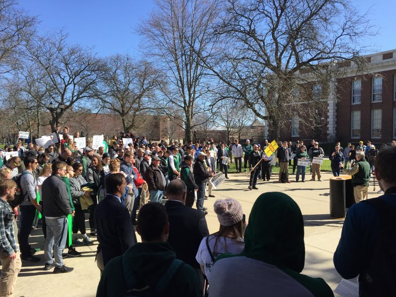 Students, alumni and supporters gather outside Welch Hall in protest of the university's decision to cut four sports from the curriculum.