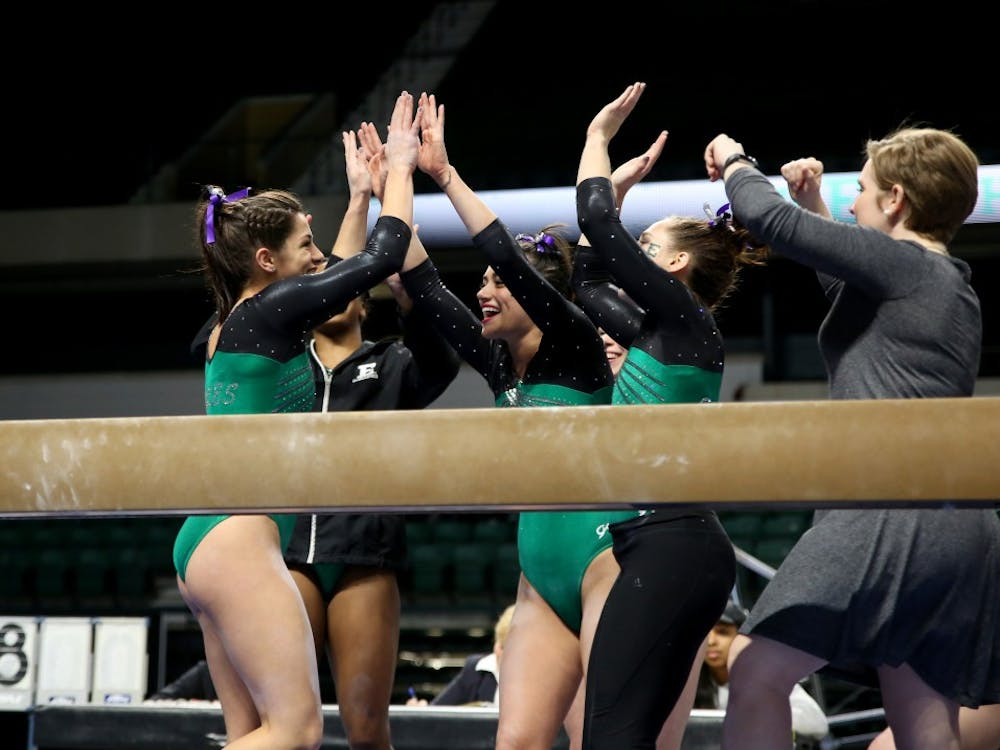 The team celebrates . against Towson at the Convocation Center on Feb. 20.