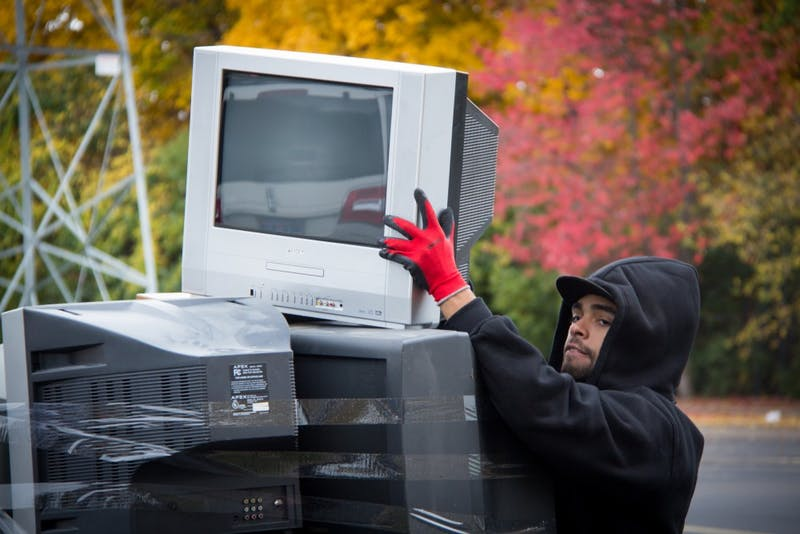 Worker stacks monitors for Eviromental Clean-up day at Rynearson Stadium in Ypsilanti, MI on Oct 18,2015