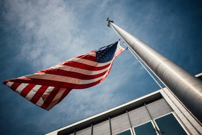 Low-angle photo of U.S. flag placed on gray pole.