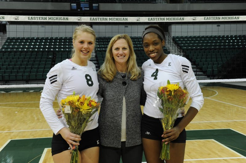 Seniors Paige Roback (8) and Erin Short (4) pose for a photo with volleyball coach Kim Berrington