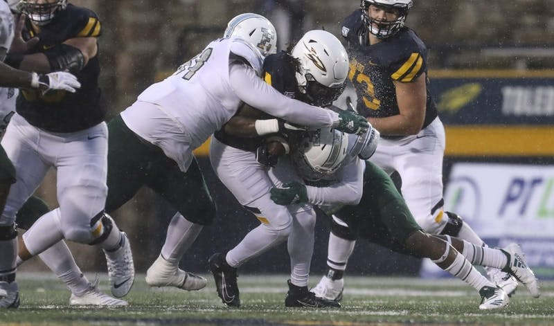 Toledo's Desmond Phillips (10) is brought down by Eastern Michigan's Aaron Hamilton (51) and Jerodd Vines (15) during a MAC football game at the University of Toledo's Glass Bowl in Toledo, Ohio on Saturday October 26, 2019. THE BLADE/REBECCA BENSON