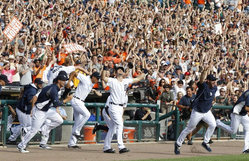 Detroit Tigers players run out of the dugout to joint the on-field celebration after their win over the Minnesota Twins clinched the American League Central Division on Sunday, Sept. 28, 2014, at Comerica Park in Detroit. (Julian H. Gonzalez/Detroit Free Press/MCT)