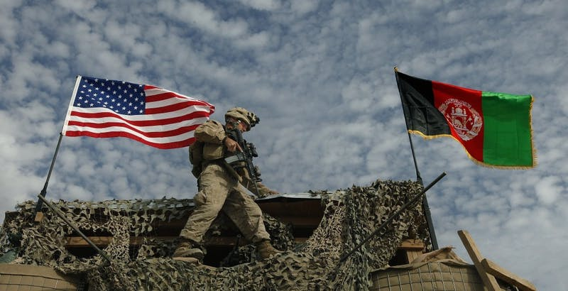 """LCpl John Westwood, of Pittsburgh, Pennsylvania, negotiates the narrow ledge of a guard tower after putting the finishing touches on the U.S. and Afghanistan flags he erected at the main gate of FOB Hassanabad which Golf Company of the 2/2 calls home in the Helmand Province of Afghanistan, December 1, 2009. He said after erecting the flag, """"I was putting up the American flag and the Afghan flag and I felt all the honor in the world to be able to do something like that- to put up our flag in a foreign country I think was a great deal. When I was finished putting those flags up... the words couldn't... can't express the way it made me feel."""" (Chuck Liddy/Raleigh News & Observer/MCT)"""