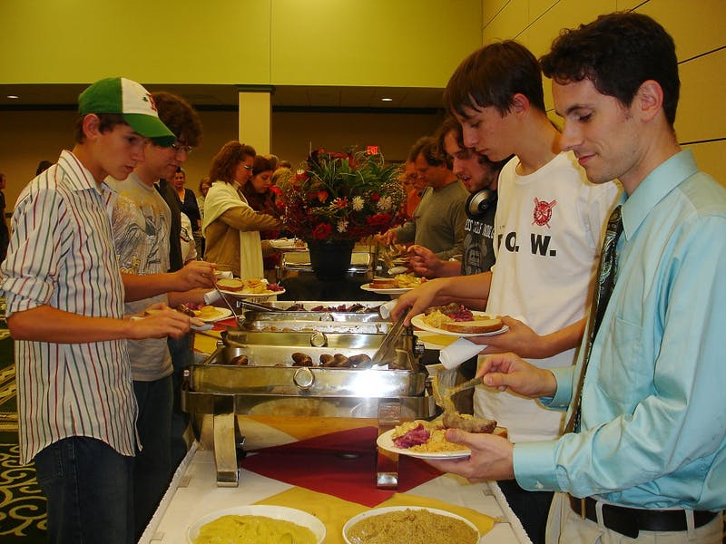 EMU alumni and current high school teacher David Baldwin (right) stands in line for food with his students at last year's German-American Day.