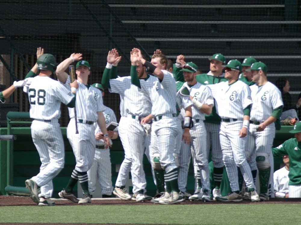 The EMU baseball team celebrates a run scored on April 7 at Oestrike Stadium.