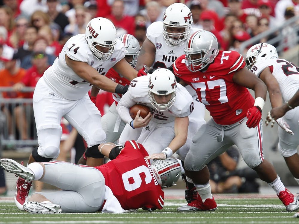 Ohio State defensive linemen Sam Hubbard (6) and Michael Hill (77) take down Northern Illinois quarterback Drew Hare (12) on a third down in the second quarter at Ohio Stadium in Columbus, Ohio, on Saturday, Sept. 19, 2015. (Eamon Queeney/Columbus Dispatch/TNS)