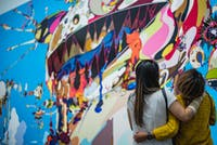 Two friends, arm in arm, looking at street art. Photo by Chris Palomar on Unsplash
