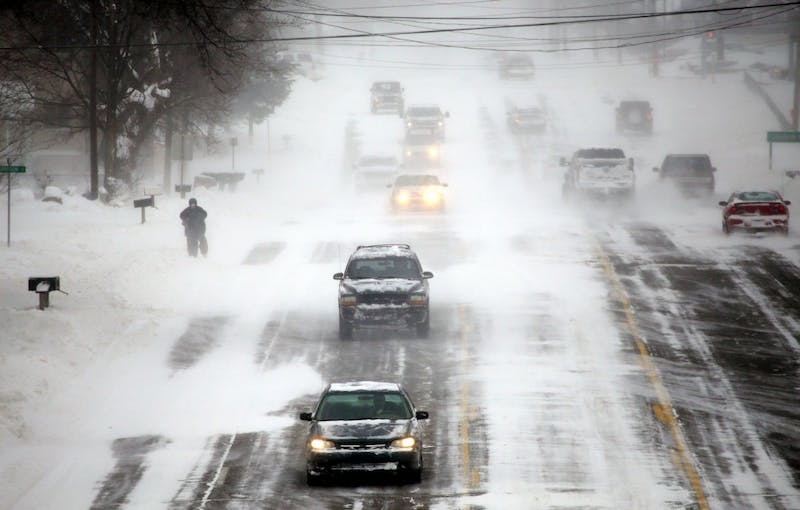 A person struggles to walk in the strong wind gusts, as vehicles pass on Bristol Road in Burton, Mich., on Monday Jan. 6, 2014. (Ryan Garza/Detroit Free Press/MCT)