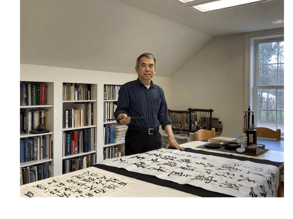 An image of professor Dr. Shinming Shyu working in his studio, engaging in the practice of traditional calligraphy to be used in a presentation for the DIA studio event (Photo courtesy of Dr. Shinming Shyu).
