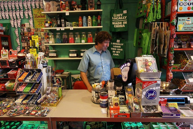 Paul Balcom, co-owner of The Rocket, stands behind the counter in his store on W. Michigan Avenue, which sells T-shirts, coffee mugs and post cards, many of which are focused on Ypsilanti.