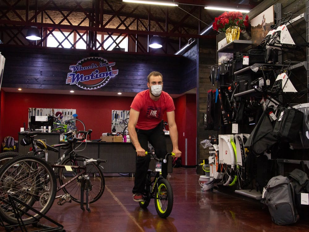 Evan Spaller, a mechanic works at Wheels in Motion, is testing a kid-bike ready for delivery.