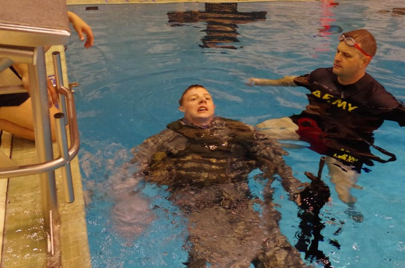 Kiley Albert, ROTC alpha company executive officer, swimming 15 meters with a dummy M16 rifle and full equipment.