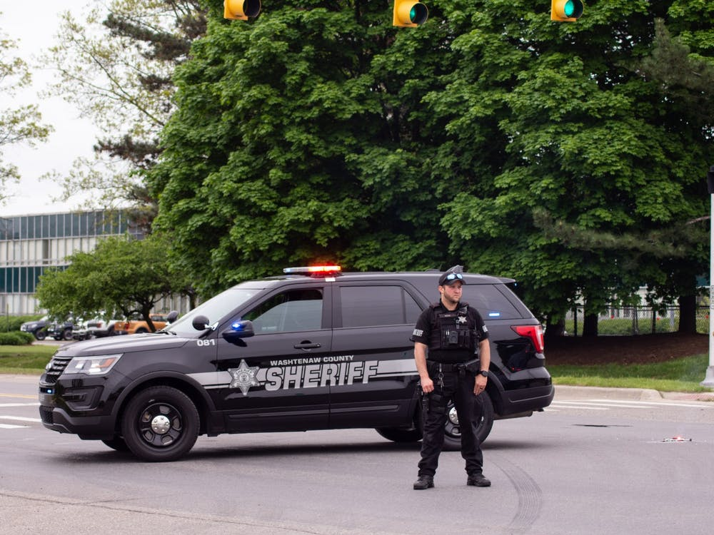 An officer for the Washtenaw County Sheriff's Department stands outside his vehicle parked on Textile Rd. in Ypsilanti during president Trump's visit to the Ford Rawsonville Components Plant on May 21, 2020.