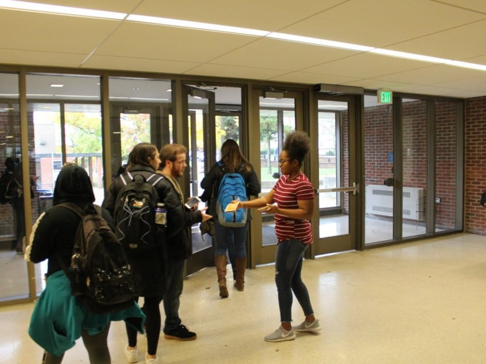 Tamia Barnes working with Michigan Student Power Network handing out information on candidates inside Pray-Harrold on Eastern's campus.
