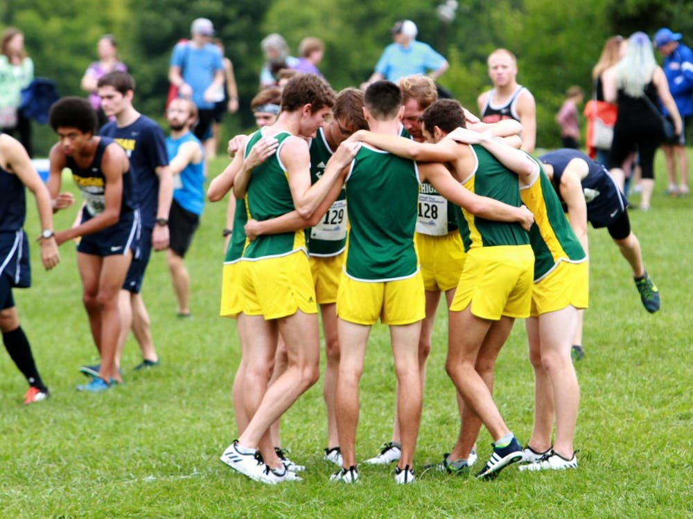 The team huddles together during the Titan Invite in Northville on Saturday, Sept. 10.