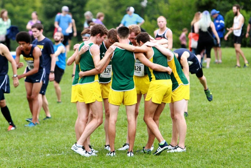 The team huddles together during the Titan Invite in Northville on Saturday, September 10.