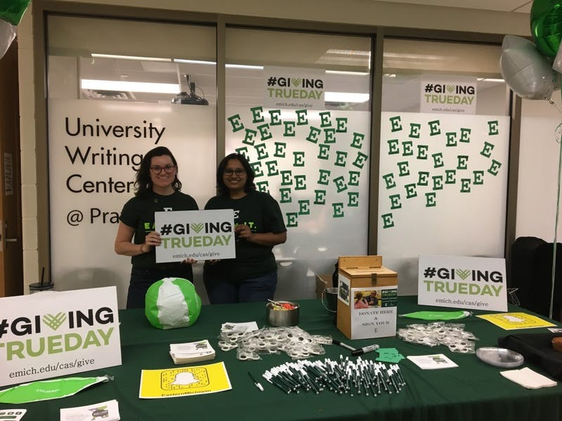 Anna Nawrocki (left) and Akshata Hiremath (right) at the college of arts and sciences giving table.