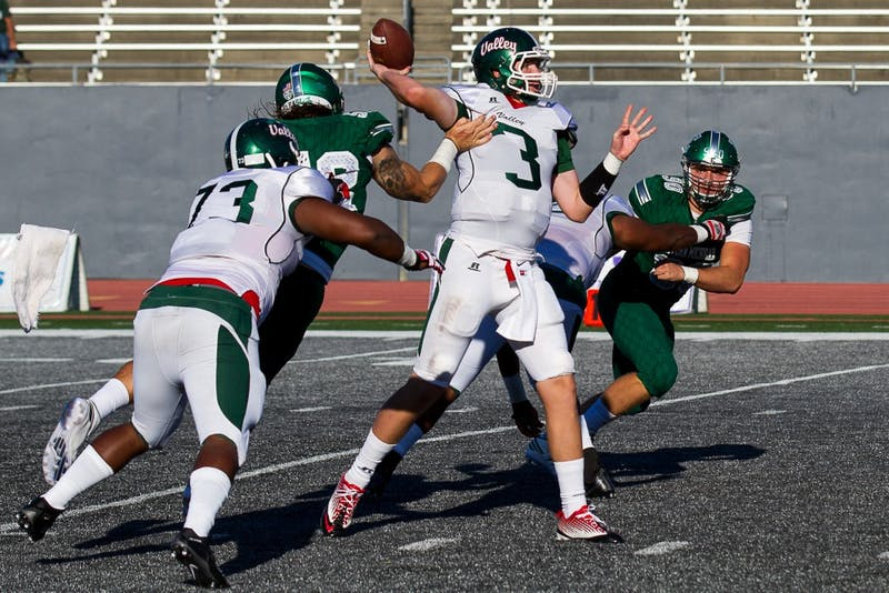 Eastern Michigan defensive lineman Pat O'Connor hits the arm of Mississippi Valley State quarterback Austin Bray, ruining a pass, during the Eagles' 61-14 win over the Delta Devils in Ypsilanti, 2 Sept.