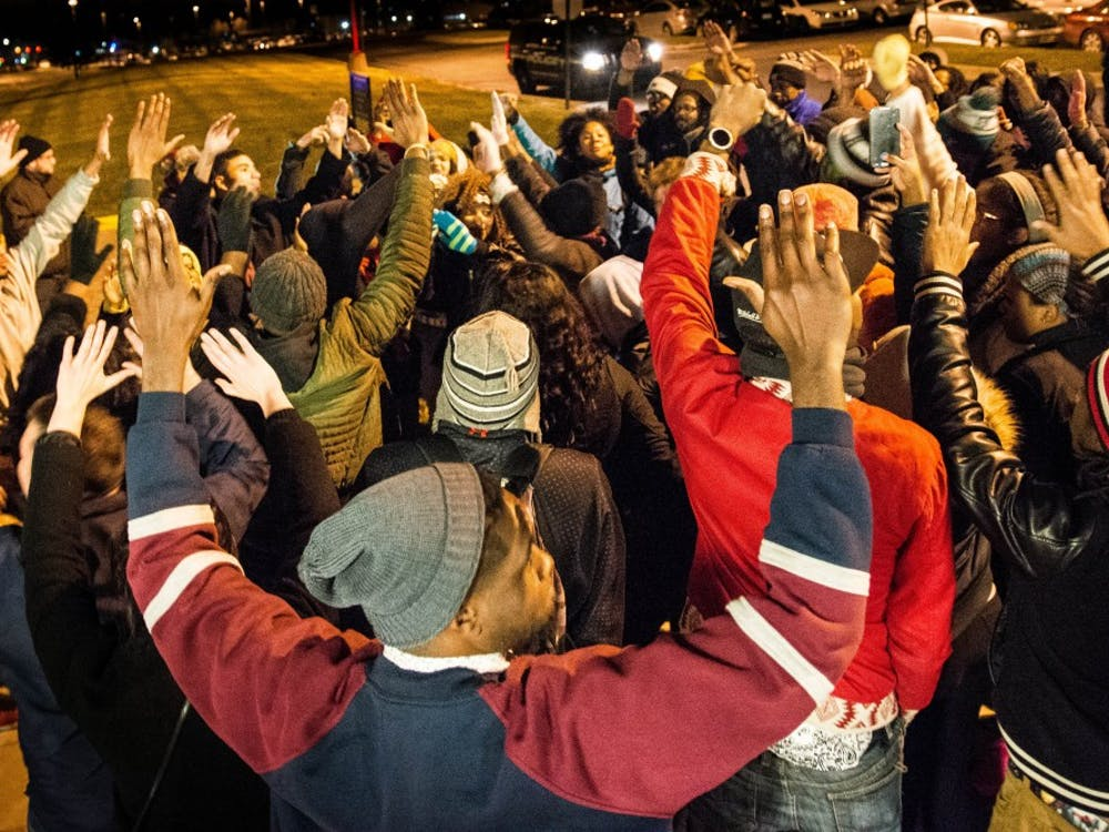 "Students chant ""hands up, don't shoot,"" during a peaceful protest of the Ferguson verdict on EMU's campus tonight. Photo by Sage Stephens."