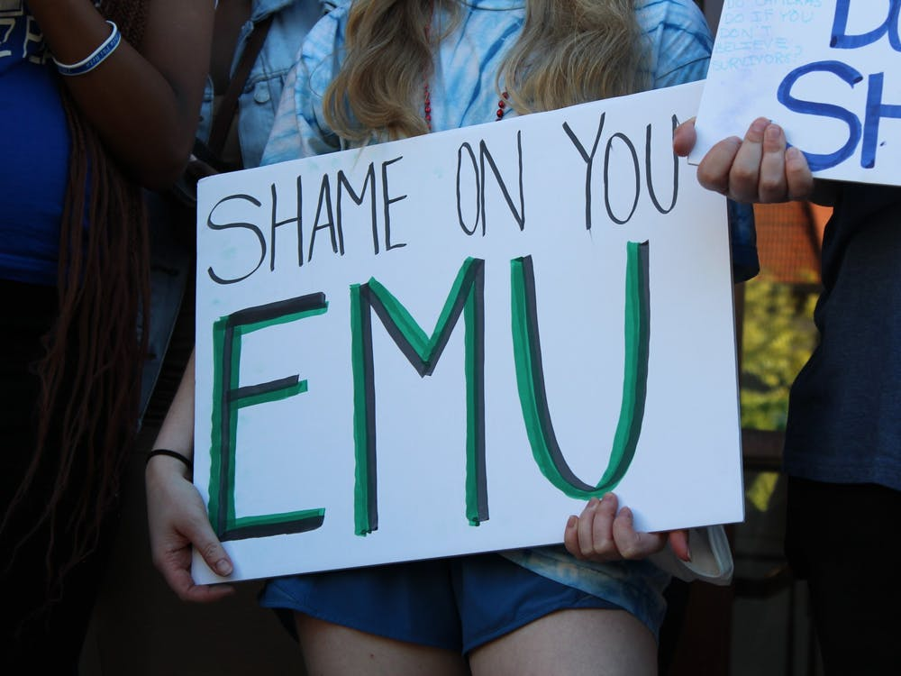 """Eastern Michigan University student hold a sign that reads """"shame on you, EMU"""" during a protest on Sept. 16."""